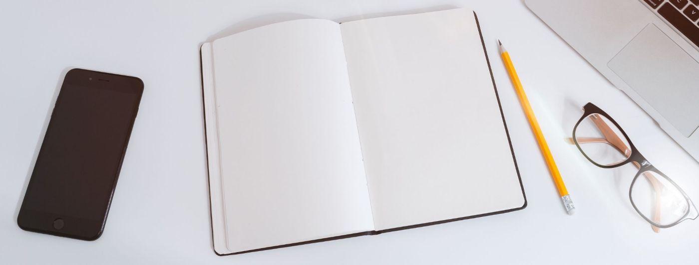 Imatge d'una taula on hi ha un telèfon mòbil, una llibreta, un llapis, unes ulleres i un ordinador portàtil