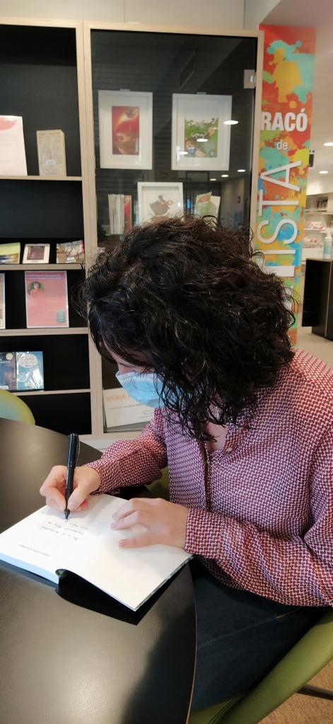 Imatge de l'escriptora Ruth Tormo signant un exemplar del seu llibre Sense codi de barres, a la biblioteca Montserrat Roig